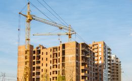 Crane build multi-storey residential house. Construction of brick house multi-storey residential building. crane build multi-storey residential house. Modern Stock Photos