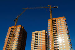 Construction of brick houses with cranes stock photo