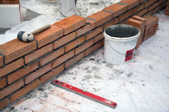 Construction of brick wall. Mallet, bucket, water-level and string royalty free stock photo