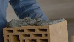 Construction of brick wall. Trowel spreading cement on bricks. Worker spreads cement for bricks Stock Image