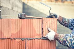 Construction bricklayer worker building walls with  bricks and mortar Royalty Free Stock Photography