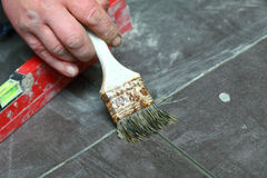 Construction brush worker is tiling at home tile floor adhesive Royalty Free Stock Photography