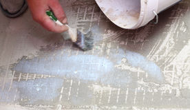 Construction brush worker is tiling at home tile floor adhesive Stock Image