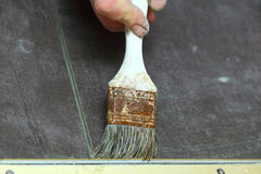 Construction brush worker is tiling at home tile floor adhesive Royalty Free Stock Image