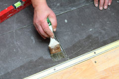 Construction brush worker is tiling at home tile floor adhesive Stock Photography