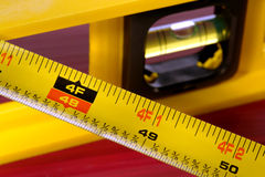 Construction Bubble Spirit Level and Tape Measure. Construction bubble spirit level and retractable tape measure with inch and foot measurement markings stock photo