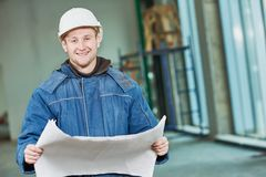 Construction builder foremaster. Young male engeneer worker foreman at a indoors building site with blueprints Stock Image