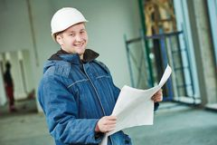 Construction builder foremaster. Young male engeneer worker foreman at a indoors building site with blueprints Royalty Free Stock Photography
