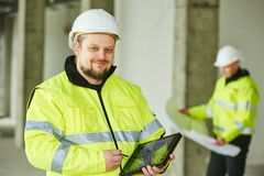 Construction builder worker at site. Young male construction engeneer worker project manager with tablet pc at a indoors building site Royalty Free Stock Photos