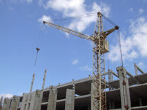 Construction of a building 3. The building crane working on construction of a building under the blue sky Stock Image