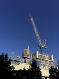 Construction Building With Crane. A crane on a construction site reaching up to the clear blue sky Royalty Free Stock Photos