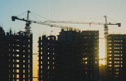 Construction of a building with cranes above sun in the background royalty free stock images