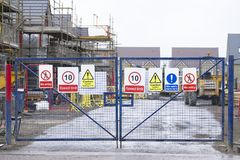 Construction building site entrance gate fence and health and safety signs. Uk stock images