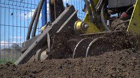 The yellow bulldozer loosens the ground, slow motion. A construction bulldozer loosens the ground and grinds stones on the construction site stock footage