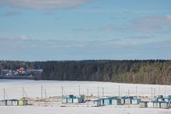 Construction cabins in the snow on the field next to the forest and the highway. construction of residential complexes in the city stock images