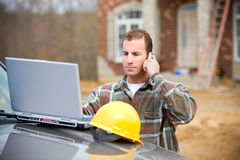 Construction: Checking Something with Manager on Phone. Series at a new home construction site.  Includes construction worker/builder, real estate agents and Royalty Free Stock Images