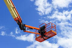 Construction cherry picker. Cherry picker work bucket platform and hydraulic construction cradle of lifting arm painted in orange and beige colors with white royalty free stock images