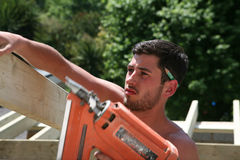 Construction Close Up. A construction worker uses a nail gun to secure roof timbers royalty free stock photography