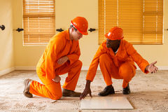 Construction co-workers discussing tiles. Professional construction co-workers discussing floor tiles stock photos