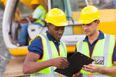 Construction co-workers discussing. About work plan construction site Royalty Free Stock Photo