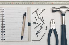 Construction background with copy space. Construction concept background with copy space. Blank note pad with empty paper sheet, pen and hammer with nails on Stock Images