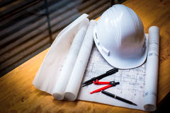 construction concept image helmet rolled blueprints on wooden bo Royalty Free Stock Images