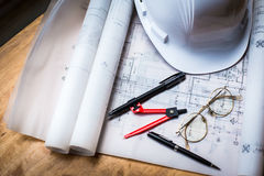construction concept image helmet rolled blueprints on wooden bo Royalty Free Stock Image