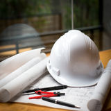 construction concept image helmet rolled blueprints on wooden bo Royalty Free Stock Photography