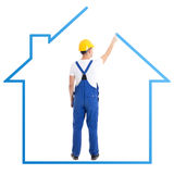 Construction concept - man in blue builder uniform drawing house Royalty Free Stock Photos