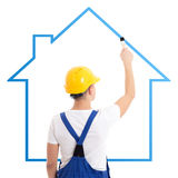 Construction concept - man in builder uniform drawing house with Stock Photo