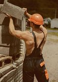 Construction concept. Man carry bricks for construction works. Builder unload truck on construction site. Construction. Worker in working uniform. Busy working stock images