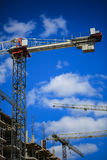 Construction concept. A new building under construction against the sky. Blue background. New urban city. Machinery. Cranes and builders on scaffolding. Heavy Royalty Free Stock Photo
