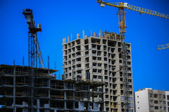 Construction concept. A new building under construction against the sky. Blue background. New urban city. Machinery. Cranes and builders on scaffolding. Heavy Royalty Free Stock Photos