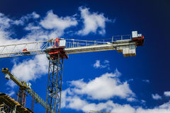 Construction concept. A new building under construction against the sky. Blue background. New urban city. Machinery. Cranes and builders on scaffolding. Heavy Royalty Free Stock Photography