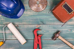Construction concept. Roller, hammer, hard hat, red adjustable pipe wrench, circular saw blade and welding mask on nice green wood Royalty Free Stock Images