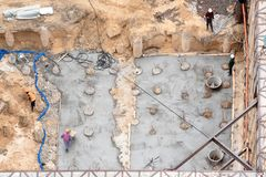 Construction of concrete foundation of new building. Aerial top view of construction site workers leveling cement in Stock Photo