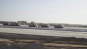Construction, concreting of airport runways, roads. Men, workers, trucks, tippers, asphalt paver, roadroller. Construction machinery works rides on runway stock video