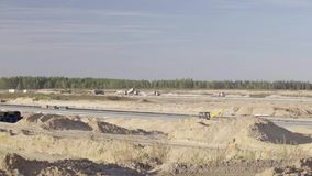 Construction, concreting of airport runways, roads. Men, workers, trucks, tippers, asphalt paver, roadroller. Construction machinery works rides on runway stock footage