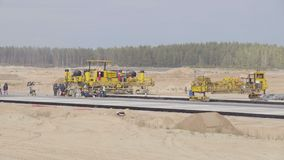 Construction, concreting des routes de pistes d'aéroport Hommes, travailleurs travaillant avec la machine à paver d'asphalte, se  banque de vidéos
