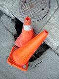 Construction cone - street big hole. Construction cone in a street big hole Royalty Free Stock Photo