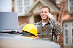 Construction: Construction Worker on Phone. Series at a new home construction site.  Includes construction worker/builder, real estate agents and young Caucasian Royalty Free Stock Photos