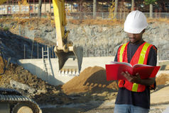 Construction contractor on site reading papers shovel Royalty Free Stock Photography