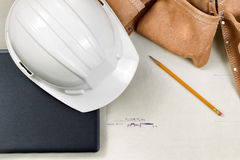 Construction contractor tools resting on top of blue print CAD d Royalty Free Stock Photos