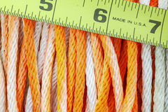 Construction cord rope measuring tape. The rope cord string of construction work with tape measurer wound on spool roll orange and white tool royalty free stock photography