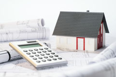 Construction costs. Symbolized by an architectural model, architectural plans and calculator Stock Photography
