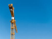 Construction Crane. A yellow construction crane against a blue sky. Room for text Royalty Free Stock Images