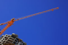 Construction crane. Against the blue sky building under construction Royalty Free Stock Images