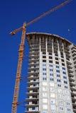 Construction crane. Against the blue sky building under construction Stock Image
