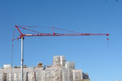 Construction Crane. A picture of a crane towering over a building under construction royalty free stock photos