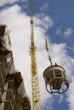 Construction crane in action. Swinging bucket around Royalty Free Stock Image